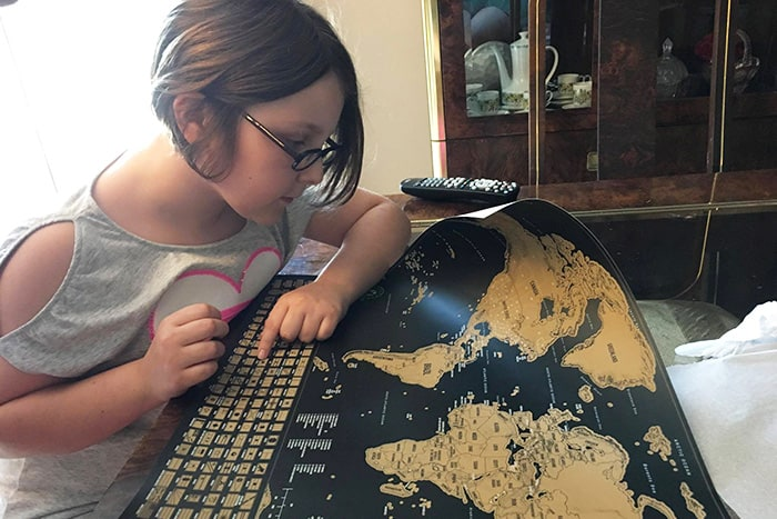 Margie's daughter, Maris, and her scratch-off world map. Photo used with permission.